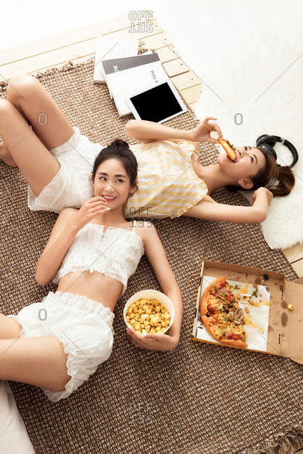 Girlfriends lying on the ground to eat snacks in the bedroom