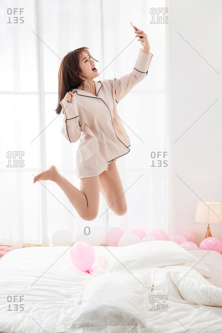 The young woman jumping on the bed