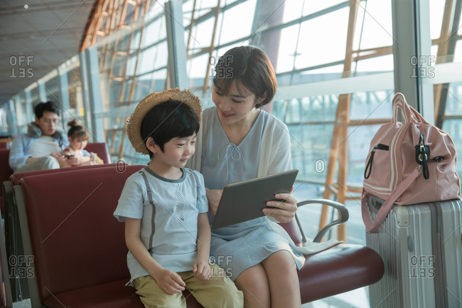 A young mother and son in the airport lounge see tablets