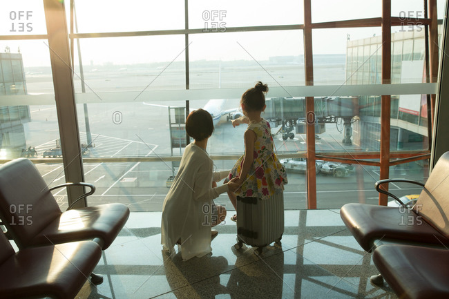 Young mother and her daughter from the airport lounge look outside