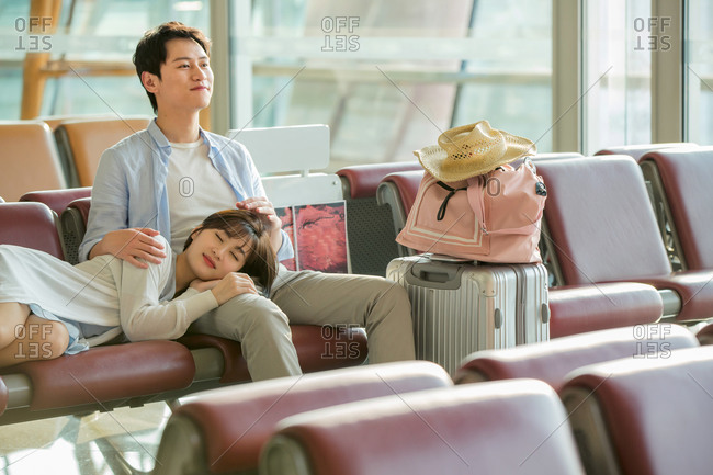 The young couple sitting in the airport lounge