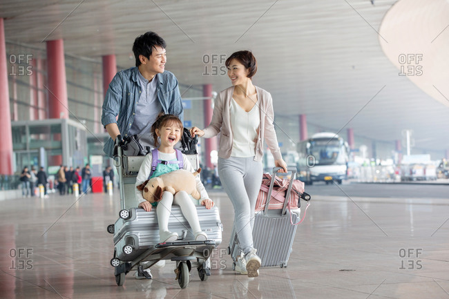 Happy family pushing baggage at the airport