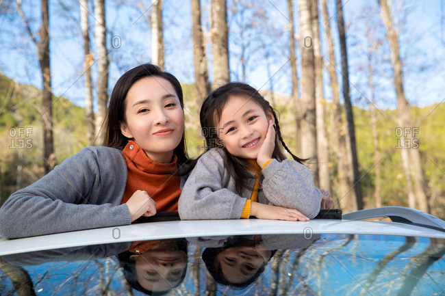 Happy mother and daughter skylight her from the car