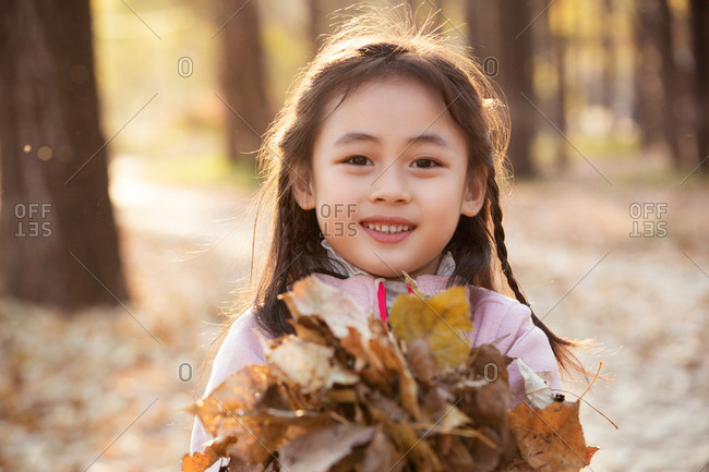 Lovely little girl picking up the leaves in the outdoor