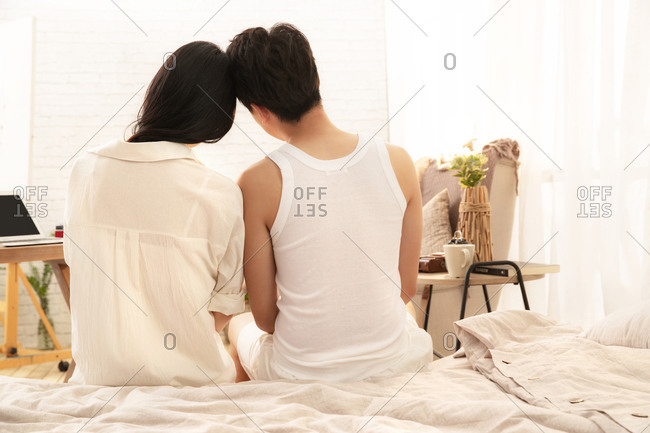 The back of happy lovers sitting on the bed