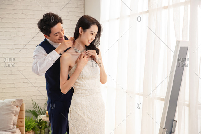 The young man to help his wife wear necklace