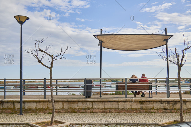 Couple on bench under large shade overlooking harbor in Tavira, Algarve, Portugal