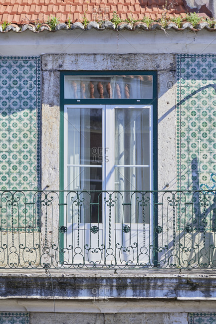 Small balcony with wrought iron railings in apartment building with Moorish tiles in Lisbon, Portugal