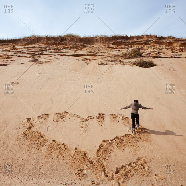 Rear View of Woman Making Heart Shape with Footprints in Sand Dune