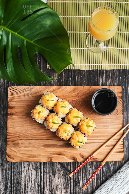 Japanese cuisine, white and black sesame sushi rolls served on a wooden table for food delivery