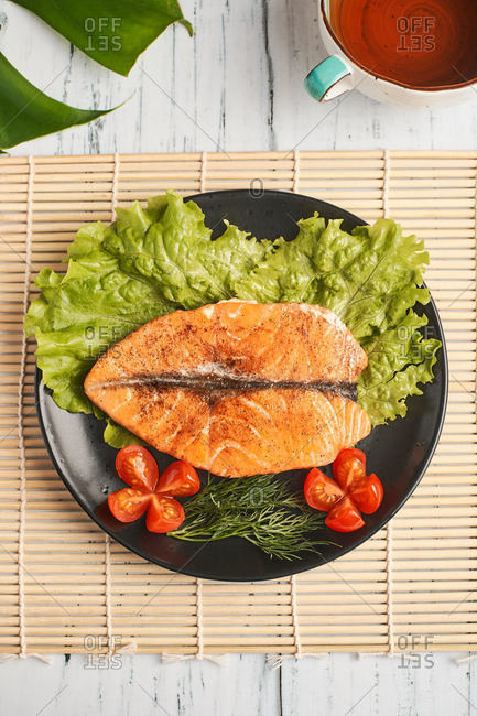 salmon fish steak in a plate with salad with cherry tomatoes healthy nutrition