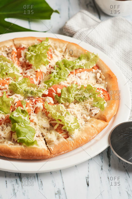 Caesar pizza with fresh salad and grilled chicken for lunch at home