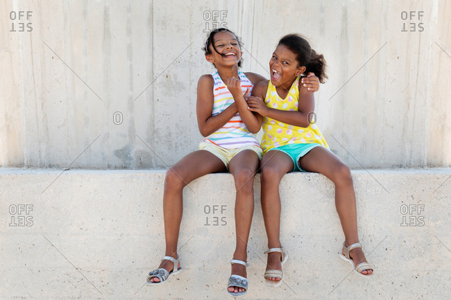 Sisters laughing together in urban environment