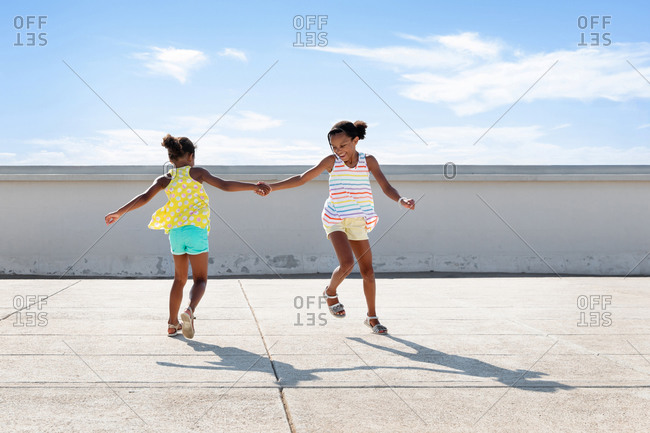 Young girls twirling in urban environment