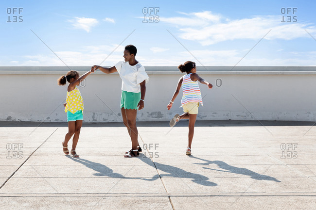 Mother and daughters dancing in urban environment