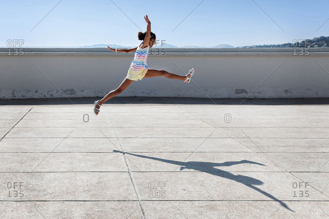 Happy young girl leaping in urban environment
