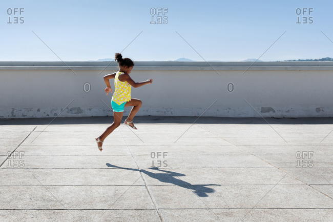 Little girl leaping in urban environment