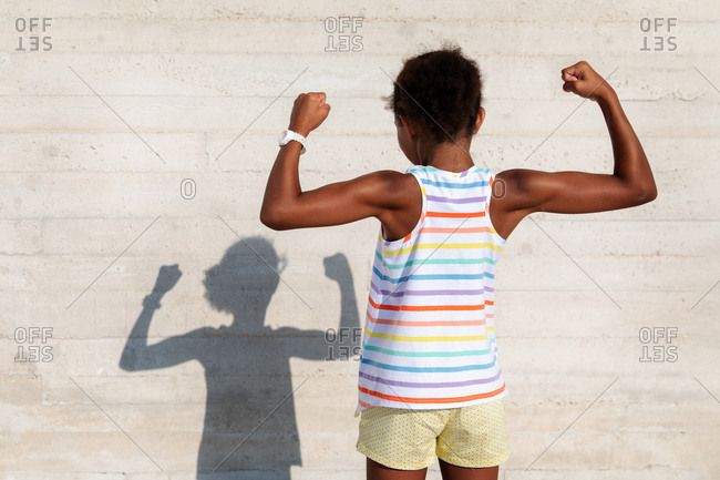 Young girl showing off her muscles playing with her shadow