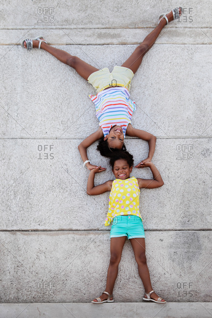 Funny sisters lying on concrete floor pretending to be acrobats