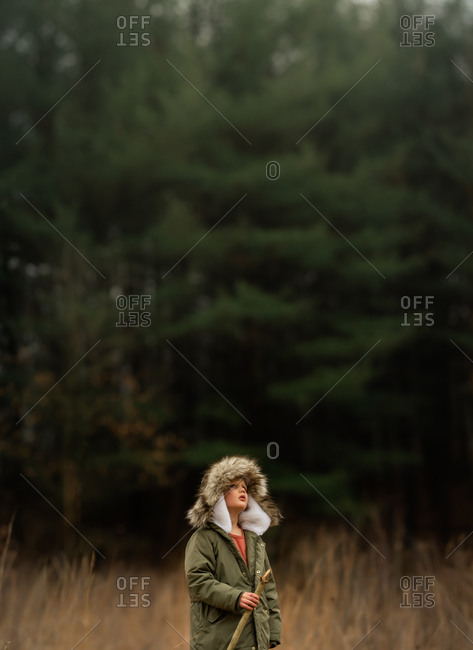 Portrait of little boy in winter gear, holding a stick standing and in front of a vast forest of evergreens