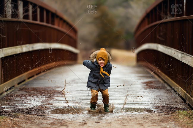 Image of little boy jumping in mud puddle with lots of excitement