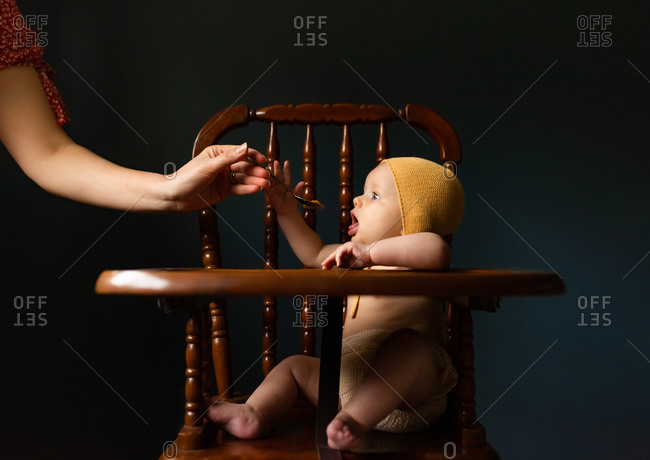 Little girl sitting in highchair reaching for spoon of food