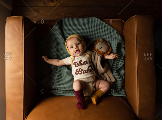 Overhead shot of baby girl lying in chair, wearing a bonnet and mismatched socks, holding a lion rag doll