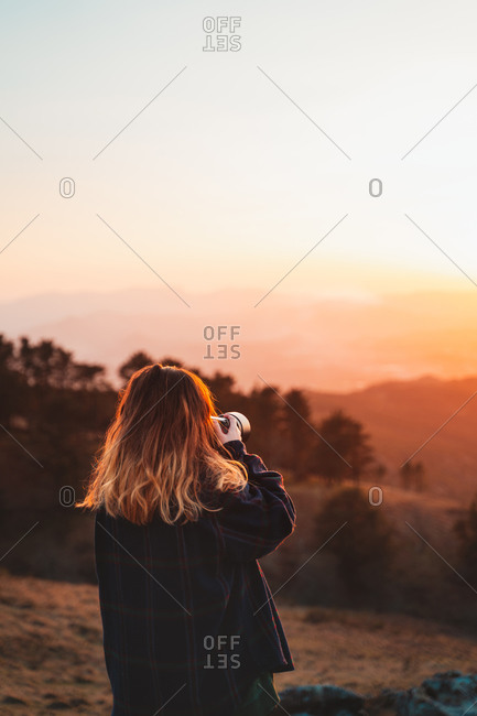 Blonde girl taking photos with the camera during sunset