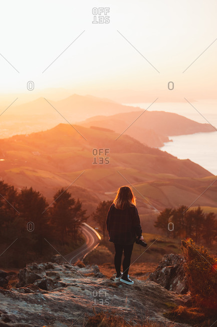 Blonde girl watching the sunset on top of a hill