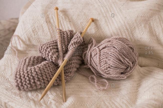 Knitting needles in yarn against a blanket