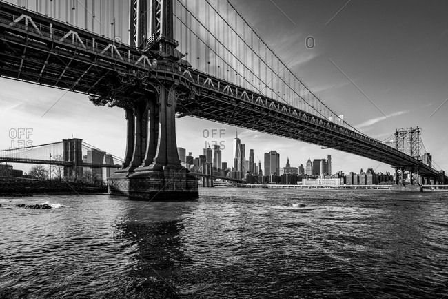New York City, New York, USA - January 9, 2020: View of the Manhattan & Brooklyn bridges and buildings in lower Manhattan in black and white