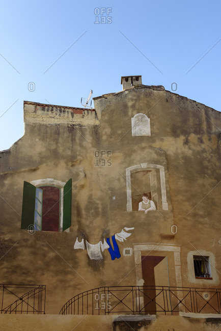 L'Isle-sur-la-Sorgue, Vaucluse, France - February 9, 2018: Painting of woman looking down at hanging laundry on side of building