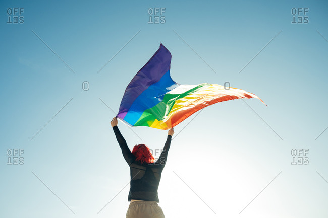 Woman holding the Gay Rainbow Flag on blue sky background. Happiness, freedom and love concept for same sex couples.