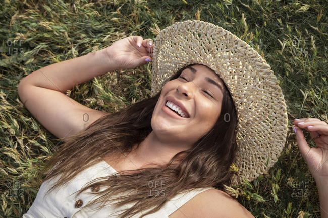 Pretty Latina woman laughing in the grass