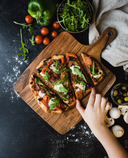 Top view of hand reaching for slice of handmade pizza on wooden board.