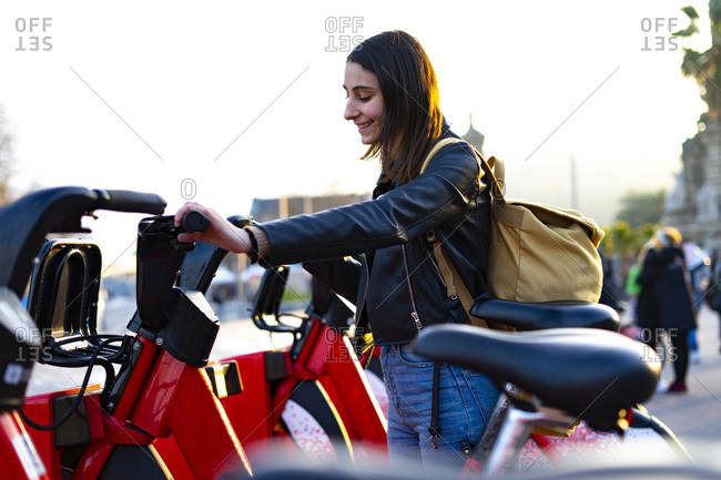 Young woman catching a red rental bike.