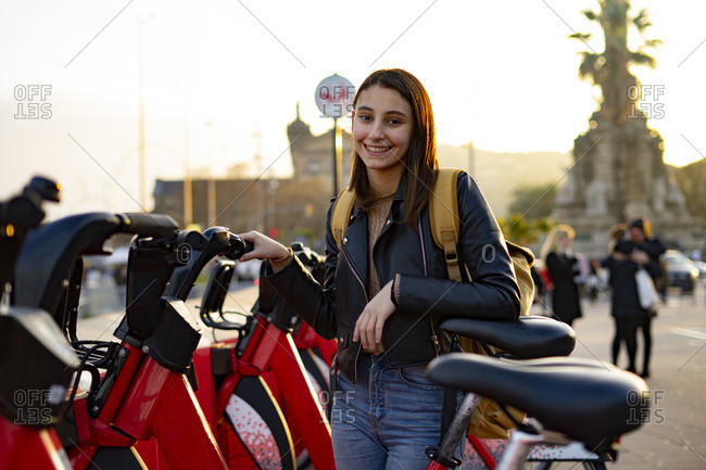 Woman smiling next to a red rental bikes.