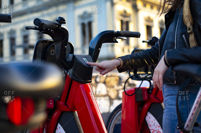 Woman lighting a red electric bike.