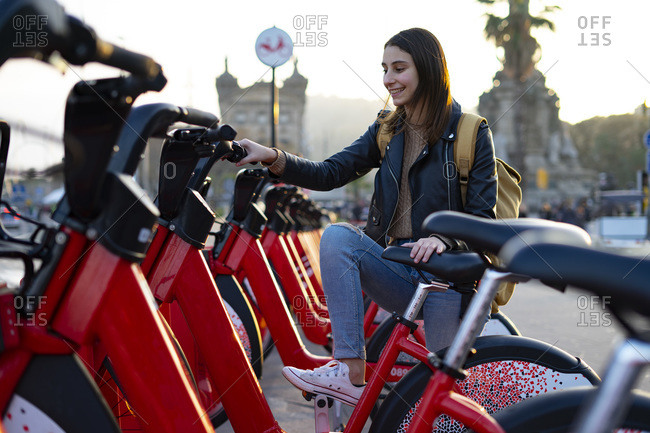 Woman climbing on a red electric bike.