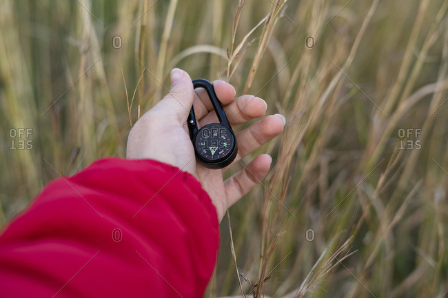 Hand picking up a black compass in the woods.