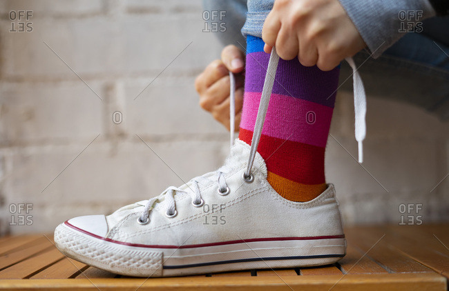 Woman tying laces of her white sneaker.