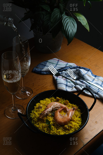 a plate of Spanish paella prepared for two accompanied by two glasses
