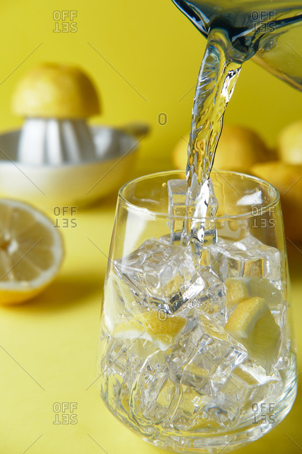 pour water into a glass with ice to make lemon water