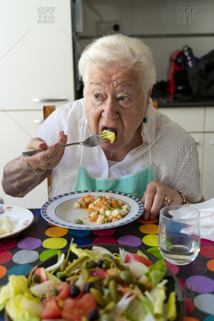 Old lady eating alone healthy food at home