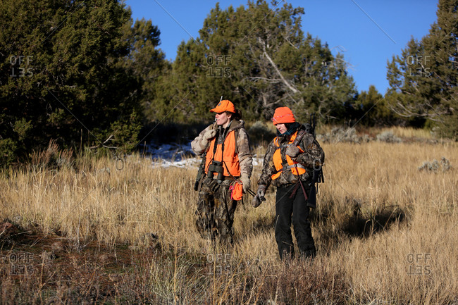 Paonia, Colorado, United States - November 15, 2015: Two female hunters hike in a meadow in Colorado