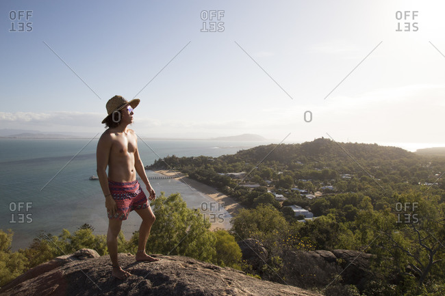 Young man with sunglasses and hat, on top of rocky hill during sunset