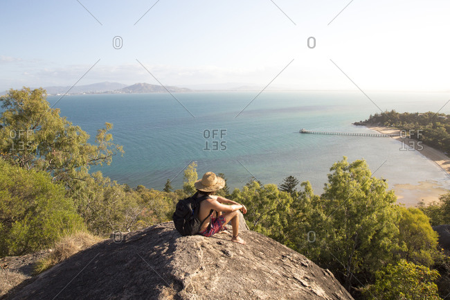 Backpacker with hat and swimsuit, on top of rocky hill during sunset