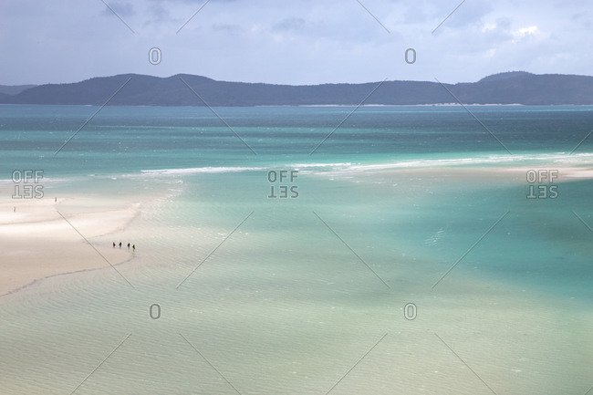 View of people walking on sandbanks next to turquoise waters