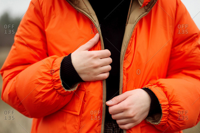 Unrecognizable female hands in bright orange jacket in winter