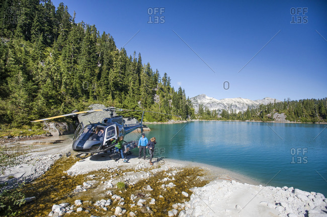 Tourist group arrives at lake via helicopter for adventure tour.